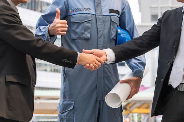 Stretta di mano di due uomini in giacca e sullo sfondo un addetto Arcobaleno Multiservice in tuta da lavoro che mostra il pollice in alto