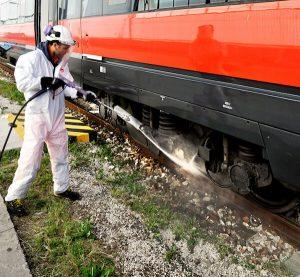 Addetto Arcobaleno Multiservice che pulisce il carrello delle ruote di un treno